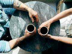 Photograph of two individuals having coffee, viewed from above the table. Photo by Joshua Ness on Unsplash.